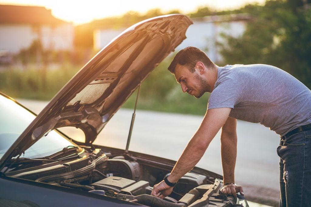 man working on car engine
