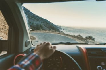 Cropped image of man driving car on road by sea